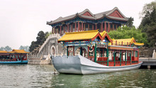 Imperial Summer Palace. Traditional Chinese-style Boats Ride Tourists On Kunming Lake.
