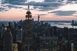 Aerial view of skyscrapers and towers in midtown skyline of Manhattan with evening sunset sky. Scenery cityscape of financial district with famous New York Landmark, illuminated Empire State Building