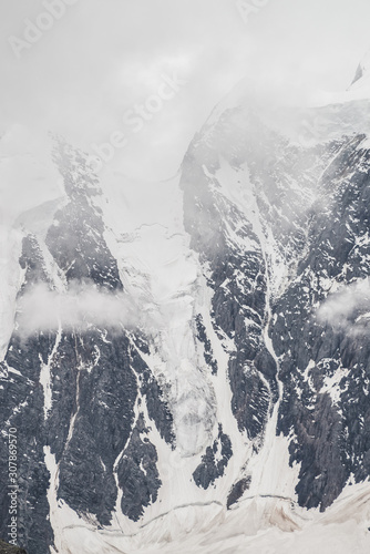 Obraz na plátně  Atmospheric minimalist textured alpine landscape with massive glacier on big mountain in low clouds