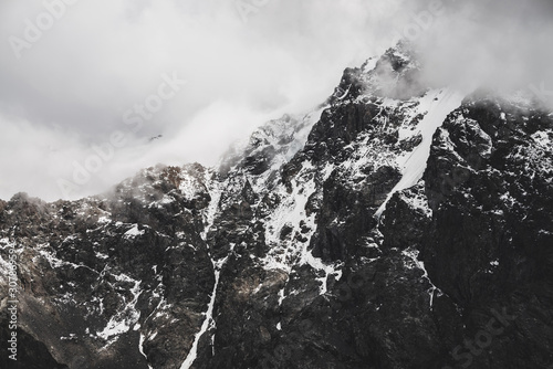 Fotografie, Obraz  Atmospheric minimalist alpine landscape with snowy rocky mountain peak