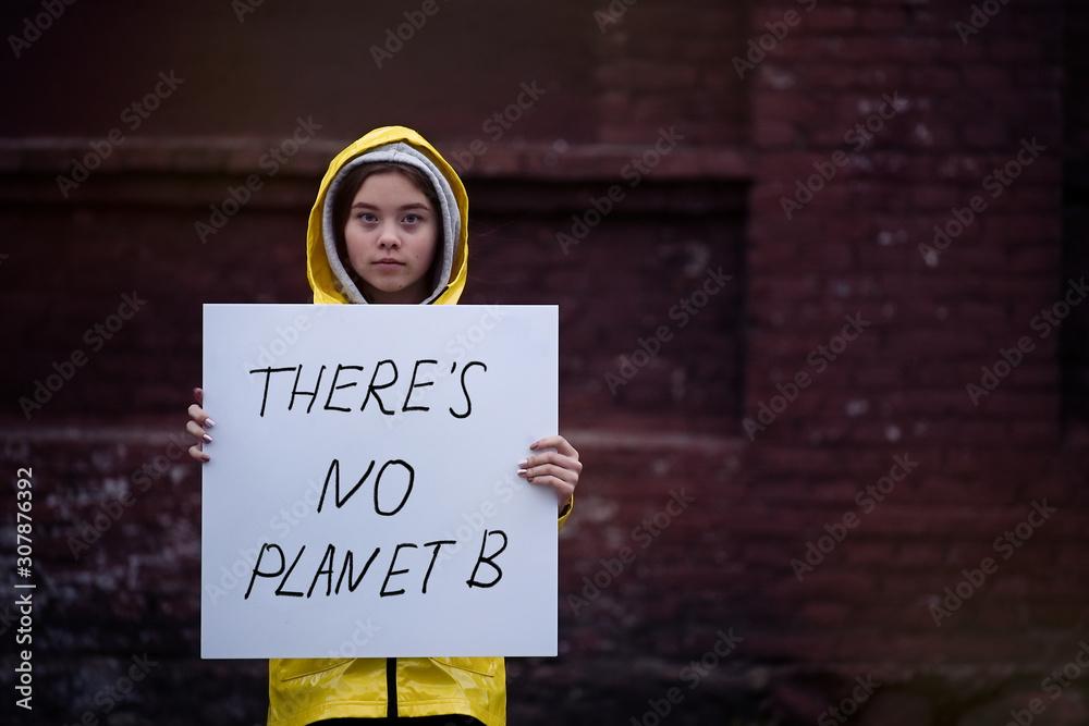 Fototapeta Teenager girl holding placard during global strike for climate change