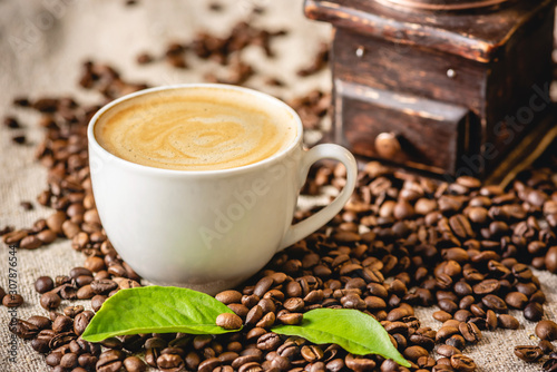 Fototapeta Cup of coffee with foam and a wooden vintage coffee grinder. Fragrant invigorating drink from freshly roasted beans. obraz