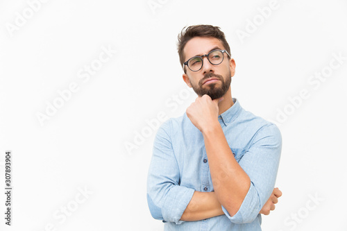 Pensive male customer looking away at copy space, touching chin, thinking Canvas Print