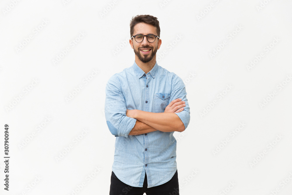 Fototapeta Happy laughing guy posing with arms folded. Handsome young man in casual shirt and glasses standing isolated over white background. Male portrait concept