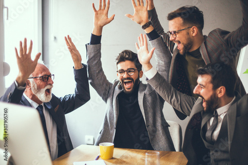 Obraz The co-workers celebrating the news of a great business achievement. - fototapety do salonu