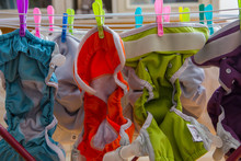 Diapers Laundry Indoors . Eco Nappy Wash Drying In A Room . Colorful Diapers Drying.Pop-in Reusable Nappy