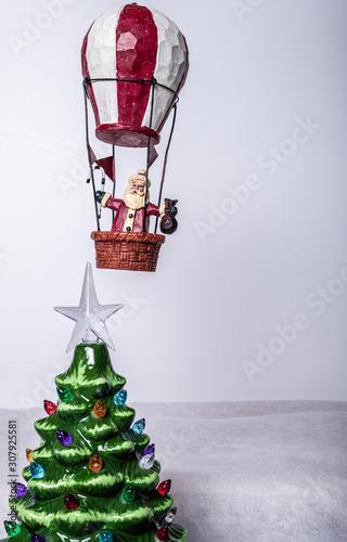 Fotografia Santa flying over Christmas tree in hot air balloon