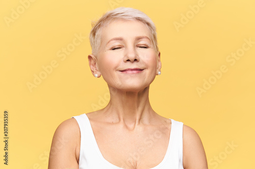 Obraz Fashionable beautiful retired Caucasian woman with pixie hairdo wearing casual clothes posing in studio keeping eyes closed and smiling with pleasure and enjoyment, listening to good music or dreaming - fototapety do salonu