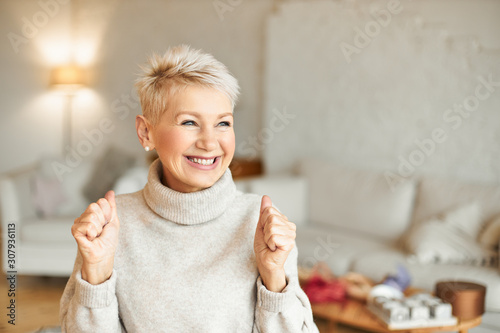 Indoor shot of fashionable overjoyed mature female in turtleneck sweater enjoying positive news, having ecstatic facial expression, laughing and clenching fists. Success and achievements concept