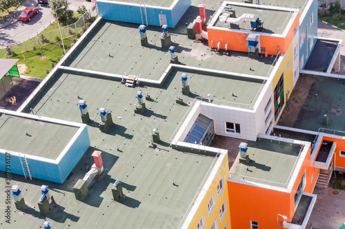 Cuadros en Lienzo Top view flat roof with air conditioners and hydro insulation membranes on top of a modern blue and orange apartment building sunny summer day