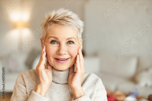 Fototapeta Surprise, amazement and astonishment concept. Beautiful blonde middle aged lady staring at camera in full disbelief, looking at something amazing, keeping hands on cheeks, can't believe her eyes obraz