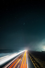Blurry Long Exposure Light Trails Of Cars Driving On A Autobahn Motorway On A Night Dark Winter Day.