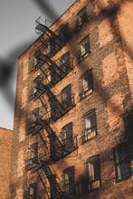 New York, December, 2017, Brick Building In Brooklyn Through A Fence