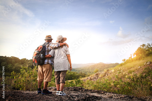 The elderly couple, hiking and standing on a high mountain, are happy in retirement.