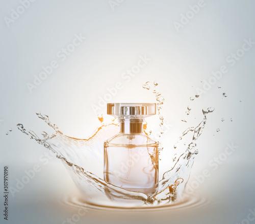 Fototapeta Bottle of perfume with splash on light background obraz