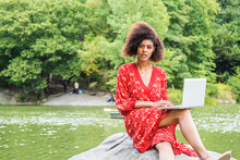 Young African American College Student With Afro Curly Hair, Wearing Red Patterned Dress, Sitting On Rocks By Lake At Central Park, New York City, Working On Laptop Computer, Looking Up, Thinking..