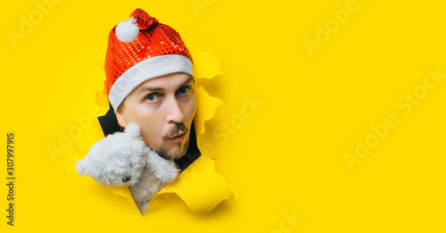 A young guy with a beard and a mustache with teddy bear in a Santa Claus or Snow Maiden hat with white pigtails peeps out of a torn hole in yellow paper Canvas Print