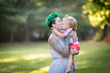 A Portrait Of Caucasian Young Woman With Green Hair And Tattoo Holding A Blond Toddler Boy In Her Hands. Hugging, Mother's Day Concept