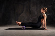Leinwanddruck Bild - Fitness woman doing stretching, warming up, pilates exercises using foam roller