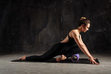 Fitness woman doing stretching, warming up, pilates exercises using foam roller