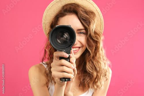 Fotografie, Tablou Beautiful young woman using vintage video camera against crimson background, foc