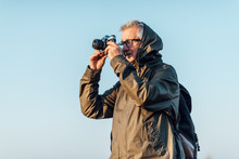 Old Man Taking Photo In Misty ...