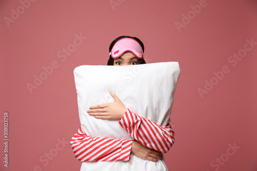 Beautiful Asian woman with pillow on dusty rose background Wallpaper Mural