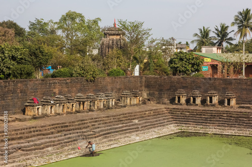Vászonkép Bhubaneshwar, Orissa, India - February 2018: An ancient Hindu temple tank lined with small shrines around the promontory above the steps that lead to the water
