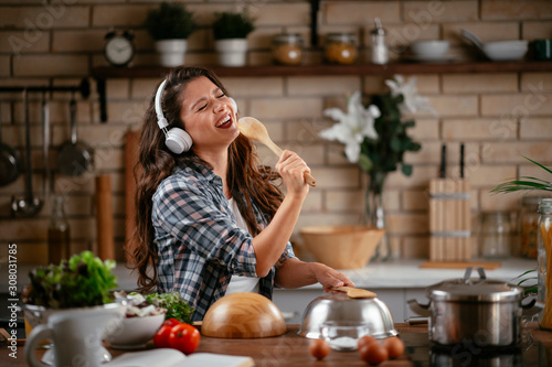 Young woman in kitchen. Beautiful woman singing and dancing while cooking. Woman listening music while cooking. - 308031785