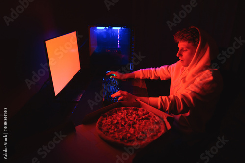 Cuadros en Lienzo Young man in a hoodie sits at work at a table with a pizza delivery box and uses a computer at night