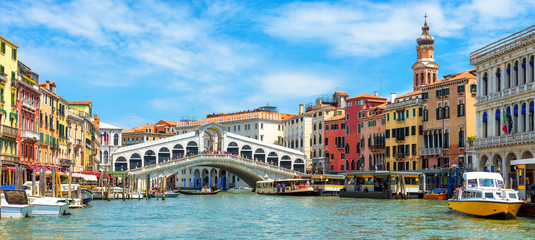 Panoramic view of Grand Canal, Venice, Italy. Rialto Bridge in the distance. It is famous landmark of Venice.