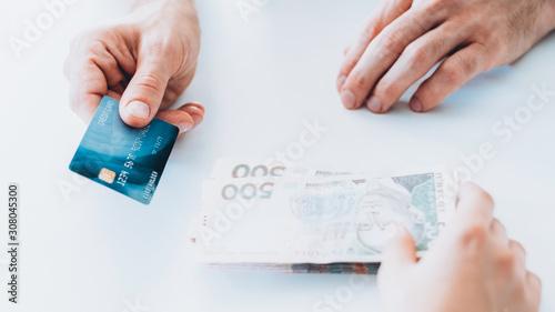 Fototapeta Bank deposit. Financial operations. Man investing money receiving credit card. obraz