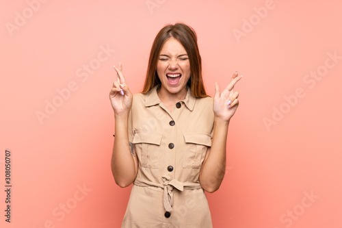 Lithuanian blonde girl over isolated pink background with fingers crossing Poster Mural XXL