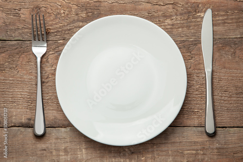 Obraz Empty white plate with knife and fork on a wooden table - fototapety do salonu