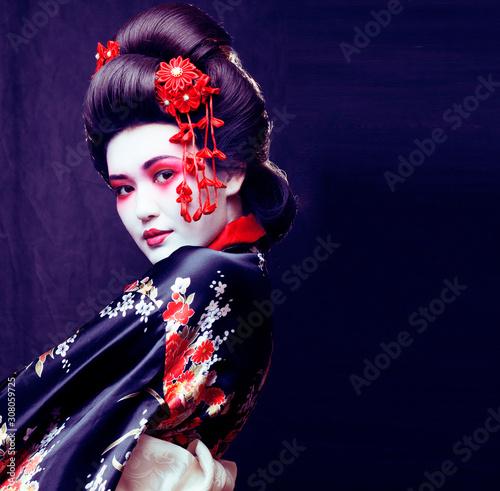 young pretty real geisha in kimono with sakura and decoration on black backgroun Fototapet