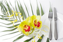 Festive Table Setting. White Plate, Knife, Fork And Two Yellow Orchids In A Vase.