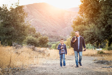 Mixed Race Father And Son Outdoors Walking With Fishing Poles