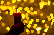 A Woman Is Holding A Red Candle In Her Hands. In The Background, Lights With Festive Bokeh Light Up. Concept: Festive Illumination