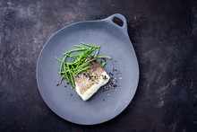 Gourmet Fried Japanese Skrei Cod Fish Filet With Glasswort And Furikake As Top View On A Modern Design Plate