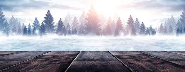 Wooden winter table. Winter empty scene, snowy trees, cold. Sunlight. Christmas day.