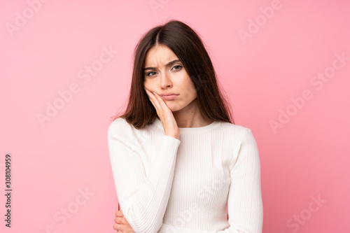 Fotografie, Obraz Young woman over isolated pink background unhappy and frustrated