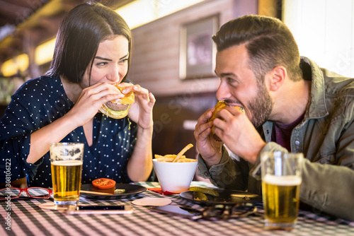 Fényképezés Happy couple having fun eating burger at restaurant pub fast food - Young people