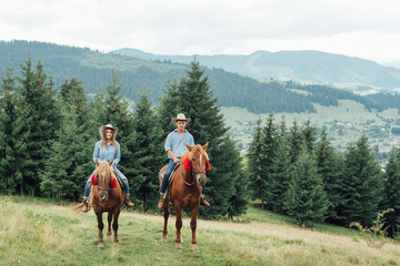 Couple riding horses in countryside tour - Happy people having fun on summer day outdoor - Vacation, excursion, healthy lifestyle, sport, love between people and animals concept
