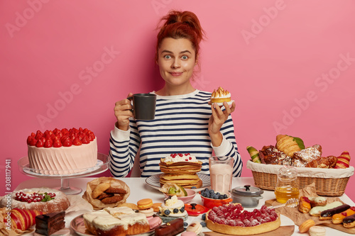 Fotografía  Ginger girl sits at festive table overloaded with many sweet desserts, eats yummy freshed baked cake and drinks tea, has unhealthy but tasty lunch, feels hungry, being voluptuous