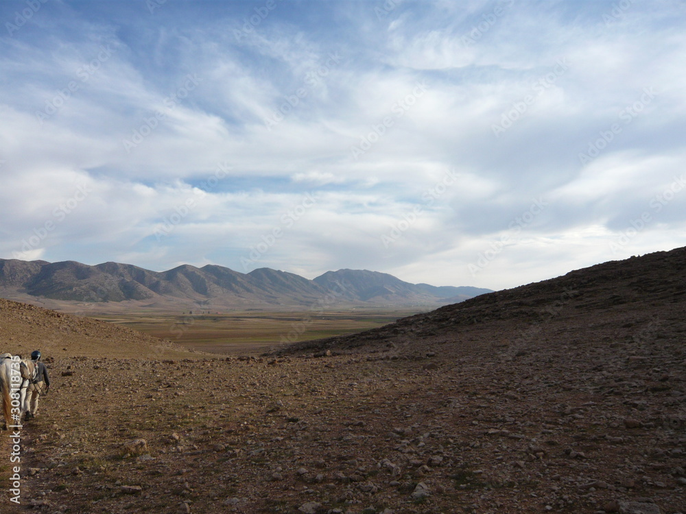 Fotografie, Obraz Walking with horse over fieldstone plain toward distant Atlas Mountains Morocco