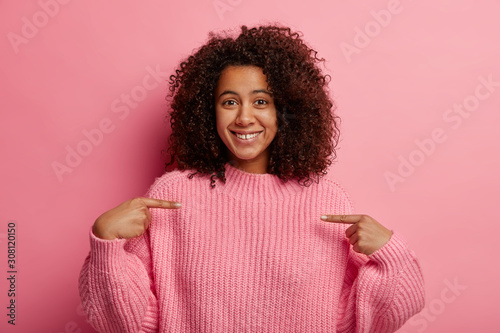 Positive Afro girl points at herself, indicates at chest, looks boastfully, dressed in oversized knitted jumper, shares good news, smiles pleasantly, isolated over pink wall, promots advertisement - 308120150