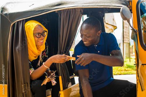 young african woman sitting in the back seat of an auto rickshaw taxi paying the Tapéta, Fotótapéta