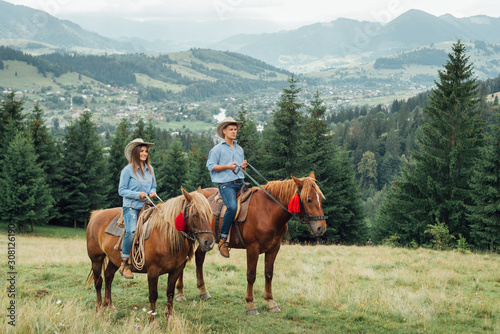 Photo a couple horseback riding from overlooking wide open field and mountains