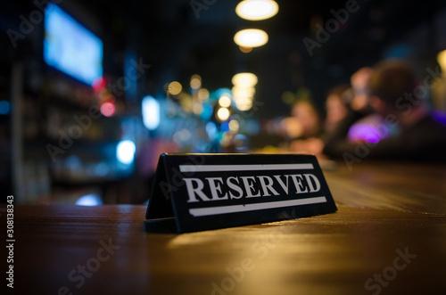 Restaurant reserved table sign standing on wooden table in bar Fototapeta
