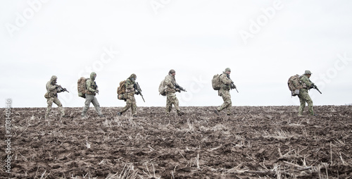 Fotomural Army soldiers group on march in muddy field